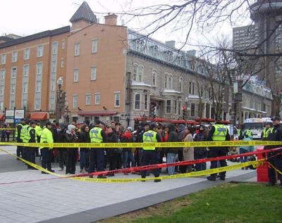 Photo: des policiers portant des dossards jaune encerclent une petite foule. Le tout est entouré de cordons plastifiés jaune et rouge. La moitée de la rue est bloquée. On voit derrière, environ 500 mètres plus loin, le Complexe G.