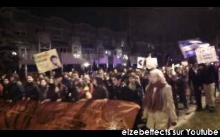 photo: la marche de nuit vue de face. Bannière rouge illisible; pancarte jaune; drapeau du Québec; plusieurs jeunes femmes
