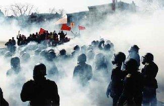 photo : de dos des anti-émeutes masqués, devant au loin une foule aux drapeaux rouges, le tout dans un nuage épais de gaz blanc