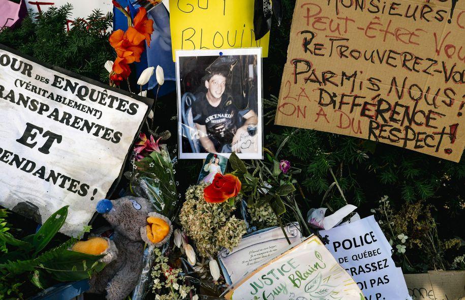 Photo : on voit de près un mémorial improvisé qui fut placé près du lieu de l'événement.  Au centre, petite photo de Guy lorsqu'il était jeune. Le tout sur un nid de fleurs avec plusieurs affiches à message autour : demande d'une enquête transparente; appel au respect des différences; « Justice pour Guy Blouin ! »; « Police de Québec, écrasez-moi pas svp.».