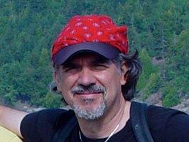 Photo : Jacques en forêt, environ 40 ans, légère barbe grise, casquette rouge en textile mou.