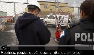 Image d'accueil de la bande-annonce, tirée du site de l'ONF. Un « foreman » et une policière regarde une jeune personne qui s'est enchaînée à une entrée clôturée.