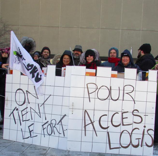 Photo : plus d'une dizaine de personnes derrière un faux fort en carton blanc avec les mots : On tient le fort  ... pour AccèsLogis. Drapeau du FRAPRU.