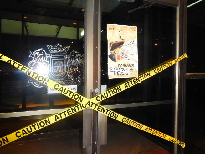Photo : porte vitrée de la Banque royale barrée symboliquement par un ruban jaune de sécurité. Il y a aussi une affiche pour l'action du 16 mars 2016 à Québec.