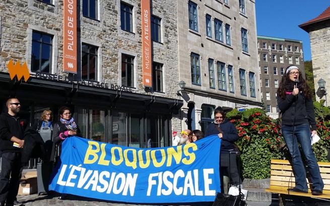 Photo : immeubles du quartier touristique près du traversier. La porte-parole du ROC 03 parle dans un micro debout sur un banc public. Banderole bleu : Bloquons l'évasion fiscale.
