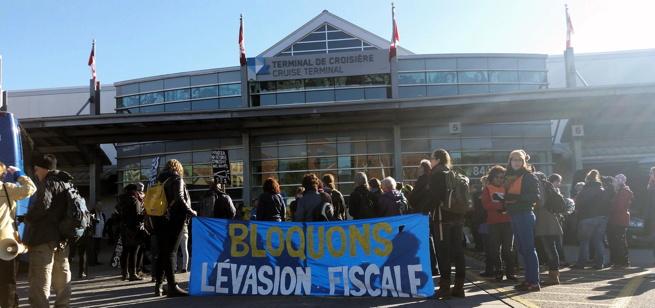 Photo : une foule devant le Terminal de croisière / Cruise Terminal, avec une banderole bleu : Bloquons l'évasion fiscale.
