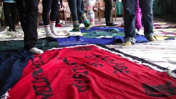 Photo : on voit les jambes d'environ sept personnes marchant sur des couvertures, donc une est en fait une bannière rouge avec une phrase (impossible à lire dans l'angle de la photo).