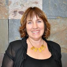 Photo : portrait d'Isabelle Riverin, formatrice. Cheveux semi-long brun-roux, chemise noire, colier de plusieurs ronds d'orés. Souriante.