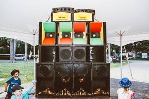 Photo de grandes caisses de son colorées du CHX Soundsystem, avec trois petits enfants qui courent autour. Sous un chapiteau blanc.