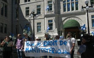 Photo : devant l'Hôtel de Ville, des employés et membres de groupes en défense de droits tiennent une bannière blanche : Pour le droit de manifester à Québec. Marie-Ève Duchesne parle au micro.