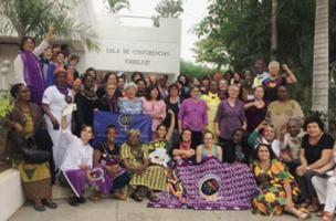 Photo de groupe au Mozambique: environ 40 femmes d'apparences très variées, plusieurs portent du mauve comme le drapeau de la MMF.</body></html>