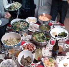 Photo : hormis quelques jambes, on voit une table couverte de nombreux plats : diverses salades, noix, lasagne végé, vin, etc.
