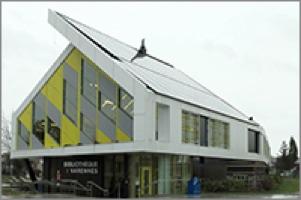 Photo d'une maison triangulaire, dont le toit n'est pas égal, car un côté est un panneau solaire plus large. Les fenêtres ont aussi un motif en triangles, de couleur jaune.