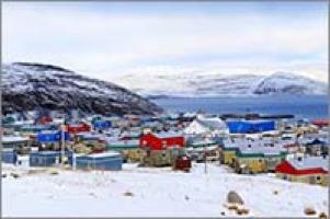 Photo de Salluit, village dans le grand nord. Petites maisons colorées, sur la neige blanche. Montagnes rocailleuses et fleuve très bleu.