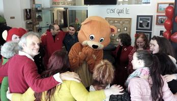 Photo de la 1ère édition : quinzaine de personnes en cercle, bras dessous, bras dessus. Ballons rouges. Mascotte d'ours caramel au milieu.