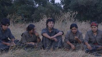 Photo de cinq femmes assises sur de l'herbe dans une forêt. Elles portent des habits vert kaki. Une parle vers la caméra, pensive.
