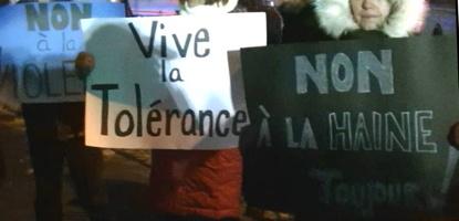 Photo de trois pancartes tenues par des personnes dont on voit seulement les manteaux d'hiver.  Non à la violence - Vive la tolérance - Non à la haine.