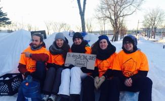Photo : cinq jeunes adultes (4 filles, 1 gars) portent des t-shirt de couleur vive orange au-dessus de leur vêtement d'hiver. Elles sont assises sur de la neige.