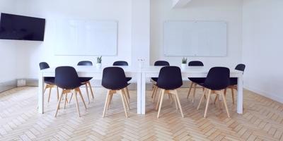 Photo : grande salle blanche propre avec deux grands tableaux blancs d'école. Il y a dix petites chaises de couleur noir autour de tables blanches ainsi qu'un écran télévisé géant suspendu dans le coin.