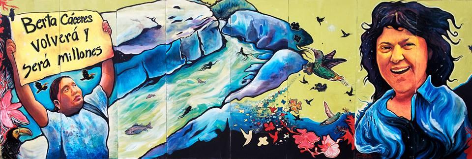 Photo d'une murale, soit une peinture colorée. Description de la peinture : à gauche, une jeune femme autochtone tient bien haut une affiche « Berta Caceres volvera y sera millions ». Au mlieu, un lac bleu, des fleurs et un oiseau. À droite, portrait de Berta souriante, avec ses cheveux noirs au vent.