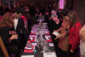 Photo : une vintaine de personnes, vêtues pour une soirée chique, se promènent autour d'une table couvertue d'objets et d'affichettes.