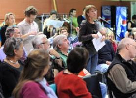 Photo d'une salle comble en 2011 lors d'une consultation qui allait transformer les Conseils de quartier et Conseils de districts électoraux. Une dame parle au micro des citoyens/citoyennes.