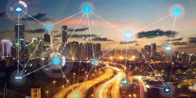 Photo d'une ville moderne la nuit, pleine de gratte-ciels de lumières. Infographie superposée d'icônes liées entre eux par des lignes blanches. Icônes : nuage, cellulaire, ondes, voiture, etc.