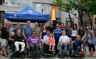 Photo de groupe sur le côté du parvis de l'église Saint-Roch : cinq hommes en fauteuil roulant, treize personnes derrière. Chapiteau bleu de la Ville de Québec.