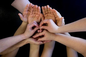 Photo d'une dizaine de mains sur fond noir.  Les mains sont placées collectivement pour représenter un visage.
