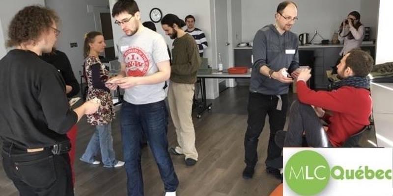Photo : neuf des participants sont visibles dans une salle. Les gens sont debouts et échangent des cartes.