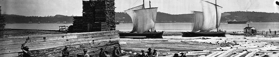 Photo ancienne (noir/blanc) : sur une large rivière ou fleuve, deux bâteaux à voiles blanches tout près d'un port où l'eau contient du bois flottant.  Un bâtiment de bois est aussi en construction.