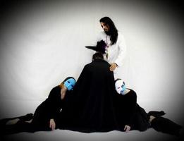 Photo conceptuel pour la pièce : trois personnes portant des capes noires et des masques (blanc et bleu), écrasées au sol une contre l'autre, l'air morose, devant un homme en blanc aux cheveux longs bruns.