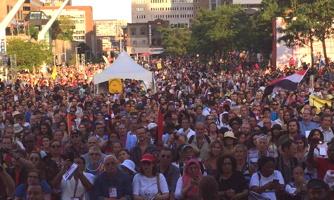 Photo de la foule devant le spectacle d'ouverture du FSM en août 2016. Foule dense et diversifiée. Rayons de soleil sur la ville de Montréal.