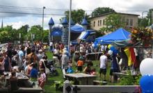 Photo : pique-nique, gazon vert, centaine de personnes, jeux gonflables bleus, tente bleue de la Ville, etc.