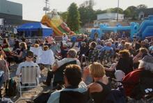Photo d'une centaine de gens sur des chaises extérieures. Jeux gonflables bleu ciel, glissade arc-en-ciel et tente bleue marine de la Ville.