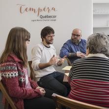 Photo : quatre personnes discutent au bord du café Tempéra Québecor. Une jeune femme, une femme plus âgée, un jeune homme et un plus âgé.