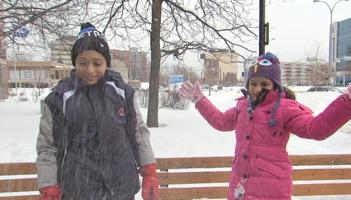 Photo d'un reportage de TVA : garçon et fillette, peau brune, devant un parc et il neige. Manteau noir et gris et long manteau rose pour la fille. L'air content.
