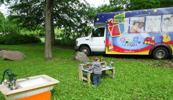Photo : parc de gazon très vert, un arbre offre de l'ombre, un tout petit garçon joue usur des objets sur une mini-table. Minibus coloré à côté. Petite fontaine d'eau fonctionnant avec une pompe manuelle.