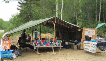 Photo d'une tente centrale du campement : grande tente ouverte, couvrant les tables pour les vives. Affiches « Non Fracturation », campagne « Vous ne passerez pas », etc.