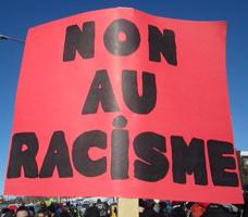 Photo d'une pancarte rouge lors d'une manif : NON AU RACISME. On discerne une foule derrière.