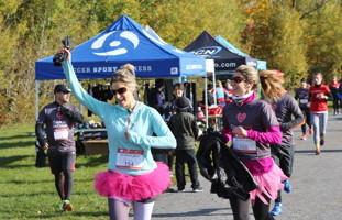Photo : deux femmes coureuses portent des tutus rose ; plusieurs derrière plus loin ; deux tentes bleues.