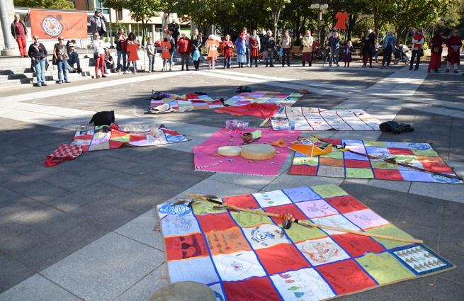 Photo : cinq couvertures courte-pointe (lire: mosaïques de carrés colorés) sur lesquelles sont écrits des messages; tambourins au milieu ; on voit une partie de la foule autour, dans un grand cercle sur la Place de L'Université-du-Québec.