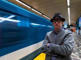 Photo : Jason Prince à côté d'un train de métro bleu qui passe rapidement. Chapeau style 1950 gris foncé, lunettes à bordures noires, veston bleu-gris, bras croisés.