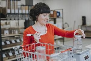 Photo : une dame, gillet orange, utilise un marqueur noir sur des pots de vitre qu'elle place sur une balance électronique. Elle est dans un magasin d'aliments santé à en juger par les légumineuse derrière elle.