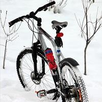 Photo d'un vélo de montagne qui se tient seul dans un tas de neige très blanche.