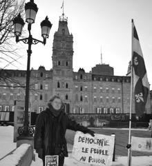Photo par Réal Michaud en noir et blanc : grand manteau de cuir noir, cheveux longs, la main sur une affiche « Démocratie - Le peuple au pouvoir », drapeau du Québec et, derrière, la façade de l'Assemblée nationale du Québec.