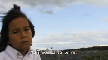 Capture-écran du film Nous sommes : garçon autochtone, cheveux dans le vent, sur un territoire sauvage à perte de vue. « Nous sommes la terre ».