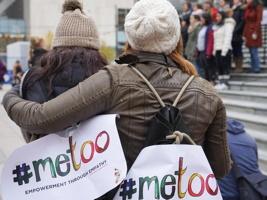 Photo : deux jeunes femmes, de dos, une soutient l'autre moralement avec son bras son ses épaules. Elles portent sur leur dos des affichettes colorées « #metoo ». Plus loin, des femmes se tiennent unies sur des marches publiques de ciment.  C'est probablement à Vancouver considérant la source sur Vice News.