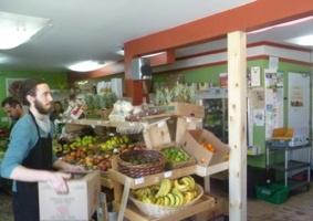 Photo : une épicerie remplie de fruits et légumes. Une jeune homme aux cheveux longs attachés transporte une boîte.