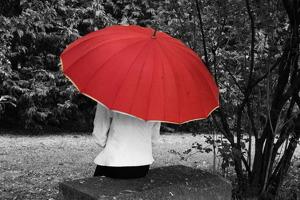 Photo en noir et blanc : une dame est assise, de dos, sur un siège carré de pierre, dans un parc entouré de verdures. Elle est cachée par un parapluie rouge (seule couleur sur la photo).